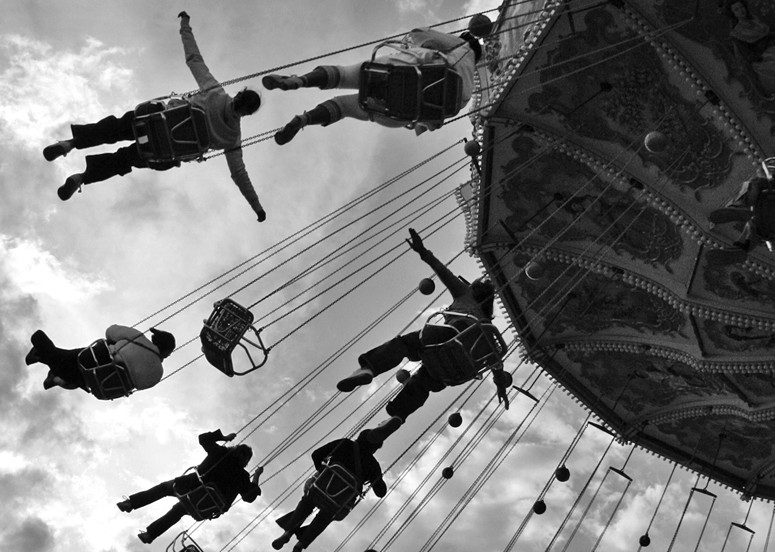 Photo of people on a chair-swing carousel, one person with arms outspread