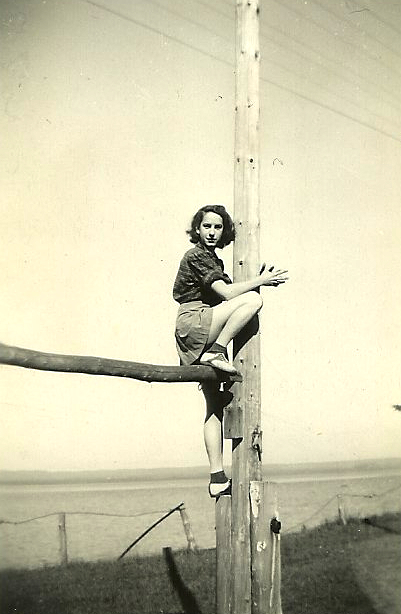 Photo of a young woman, perched high atop a fence, taken in the early 1940s.